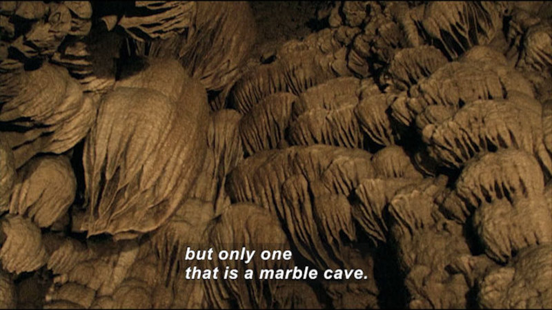 Domed, dripping rock structures line the wall of a cave. Caption: but only one that is a marble cave.
