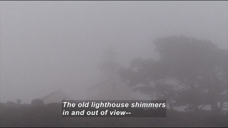Lighthouse with outbuilding and trees as seen through dense fog. Caption: The old lighthouse shimmers in and out of view--