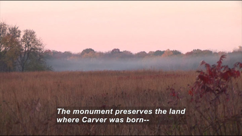 Open field of dry, brown grass with mist hovering above it. Caption: The monument preserves the land where Carver was born--