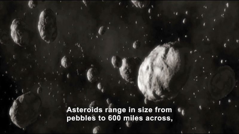 Asteroids floating through the galaxy. Caption: Asteroids range in size from pebbles to 600 miles across,