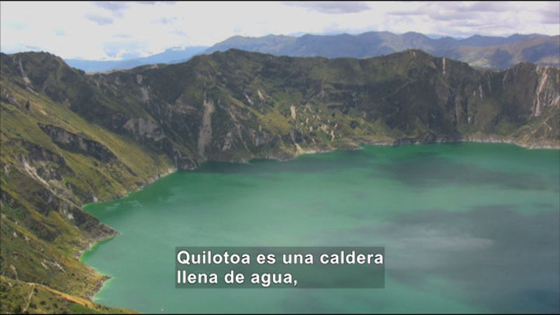 Basin of a volcano filled with water. Spanish captions.