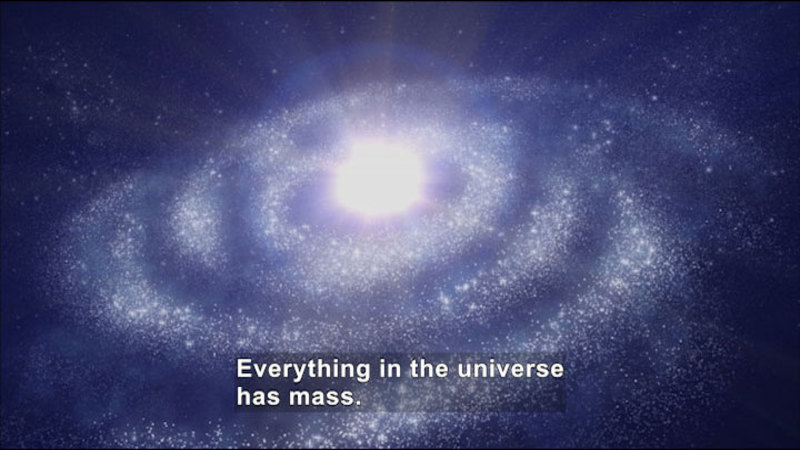 The universe swirling and glowing. Caption: Everything in the universe has mass.