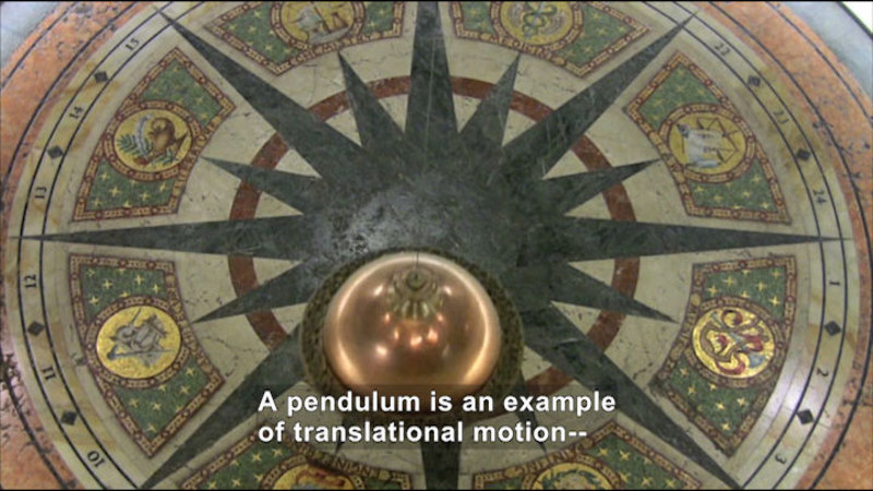 Ornate floor tile with a pendulum swinging above. Caption: A pendulum is an example of translational motion--