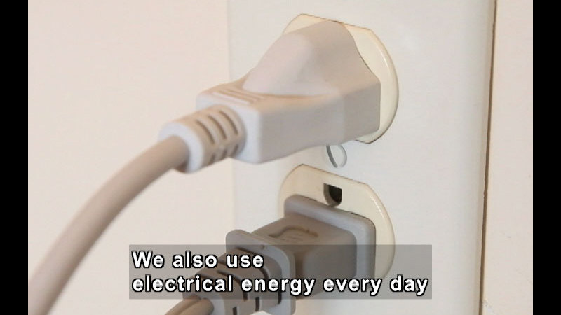 Two power cords plugged into a wall outlet. Caption: We also use electrical energy every day