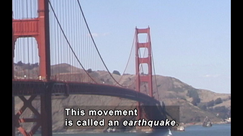 Rolling brown foothills ending in San Francisco Bay with the Golden Gate bridge in the foreground. Caption: This movement is called an earthquake.