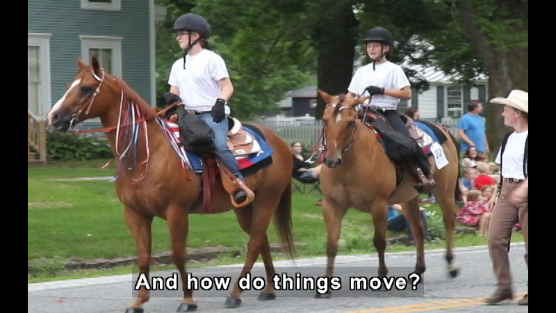 Two people riding horses while someone walks beside them. Caption: And how do things move?