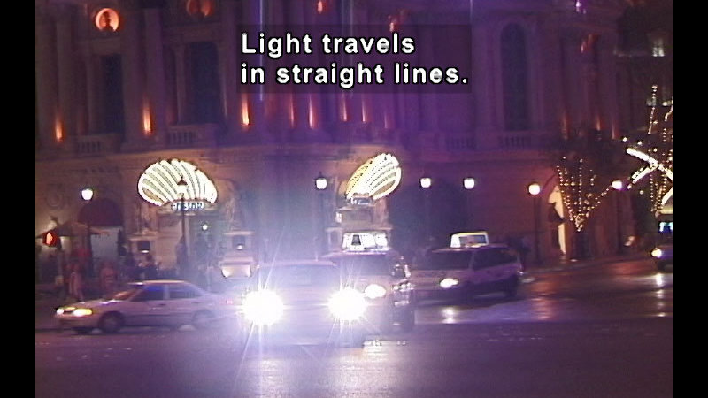 Straight on view of a car's headlights. Caption: Light travels in straight lines.