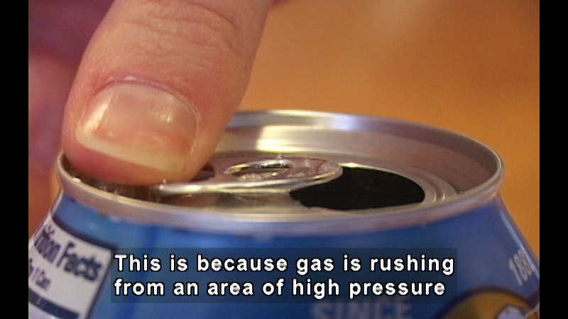 Open aluminum can. Caption: This is because gas is rushing from an area of high pressure