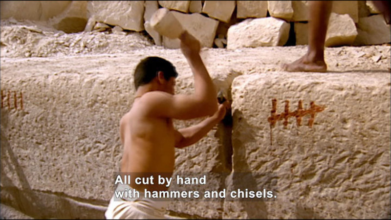 """Person in a loin cloth chiseling a large block of light-colored stone. The block has hashmarks representing """"5"""". Caption: All cut by hand with hammers and chisels."""