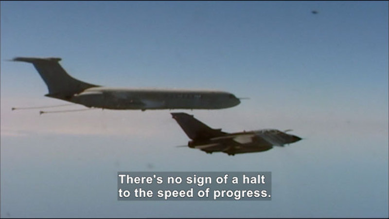 A large jetliner flies above and very close to a smaller, angular space craft. Caption: There's no sign of a halt to the speed of progress.