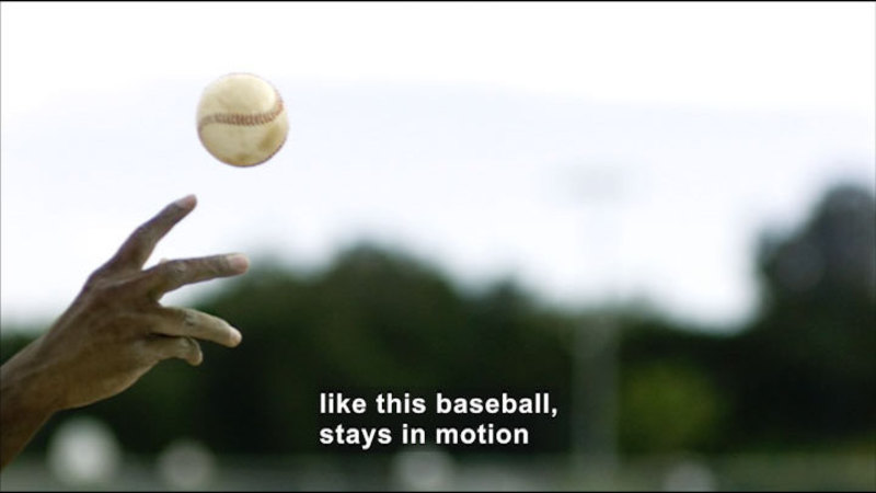 A baseball being thrown. Caption: like this baseball, stays in motion