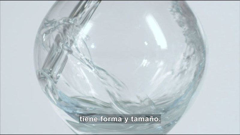 Water pouring into a glass. Spanish captions.