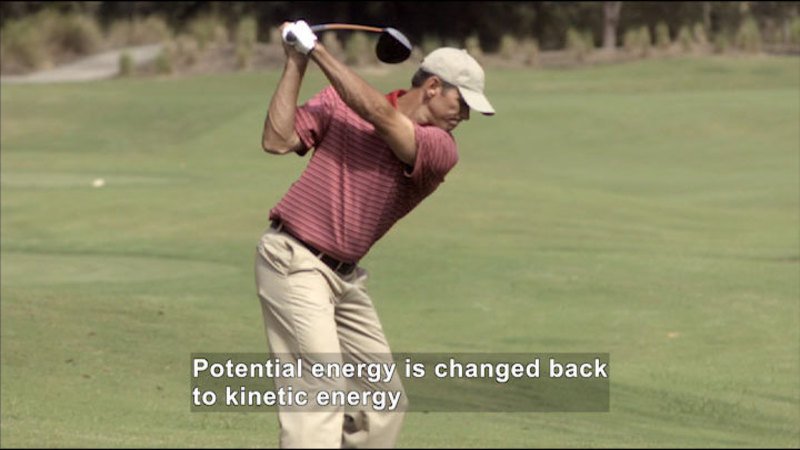 A man golfing. Caption: Potential energy is changed back to kinetic energy