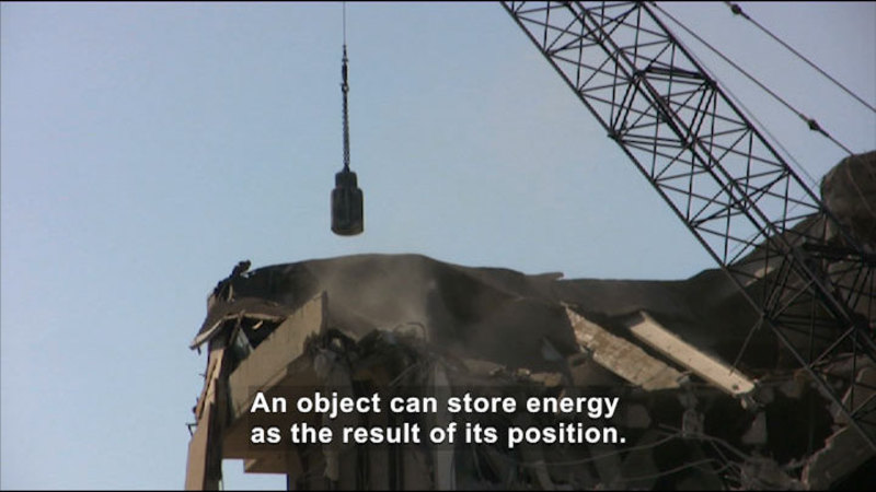 A crane demolishing a building. Caption: An object can store energy as the result of its position.