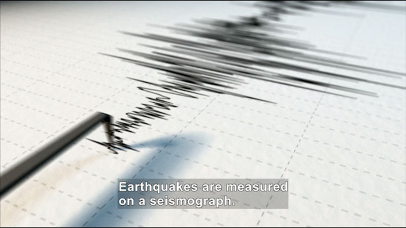 A needle scratching measurement onto paper. Caption: Earthquakes are measured on a seismograph.