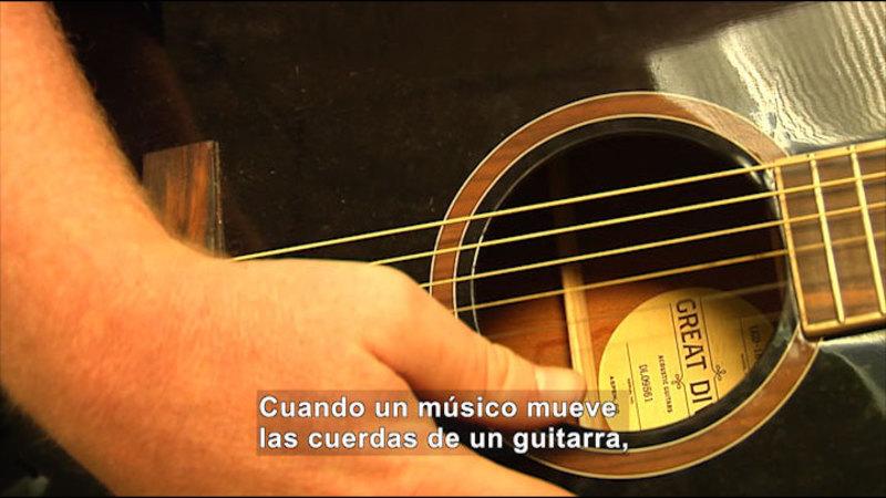 Close up view of man strumming guitar. Spanish captions.