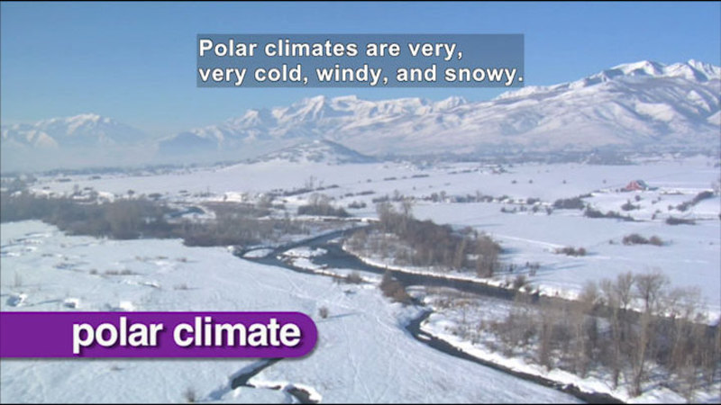 Snowy field and mountain range. Caption: Polar climates are very, very cold, windy, and snowy.