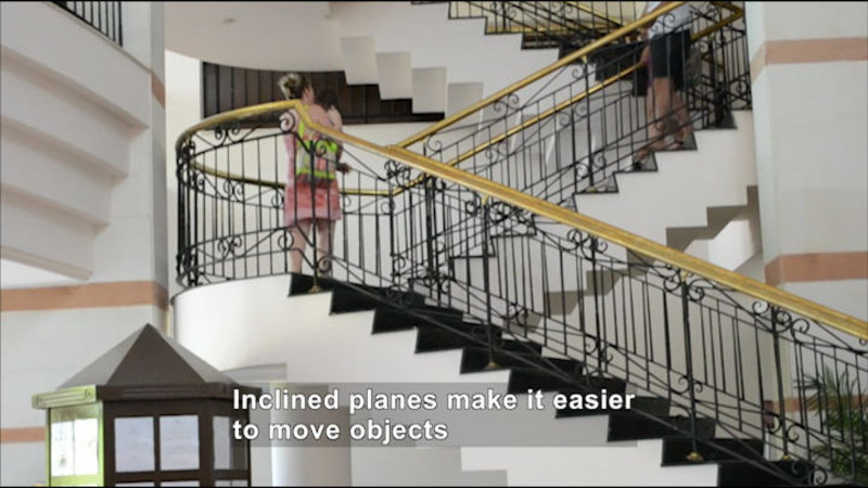 People climbing up a staircase. Caption: Inclined planes make it easier to move objects.