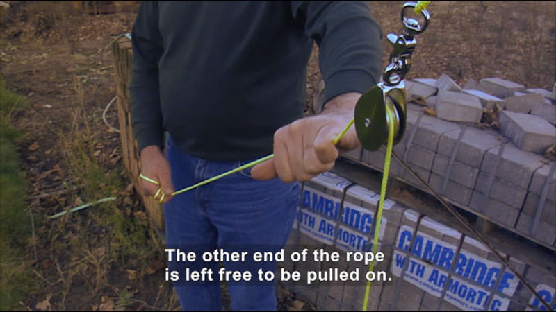 A man using a pulley. Caption: The other end of the rope is left free to be pulled on.