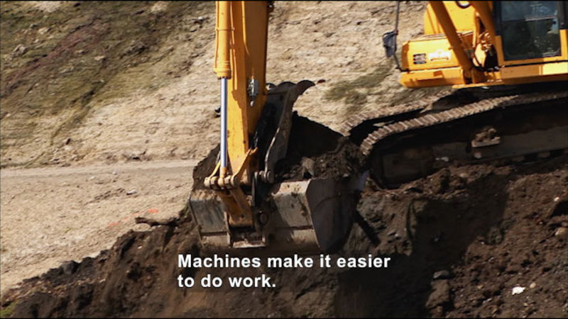 Large machinery scooping dirt. Caption: Machines make it easier to do work.