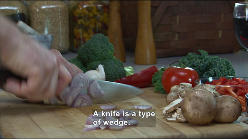 A knife on a cutting board chopping onions. Caption: A knife is a type of wedge.