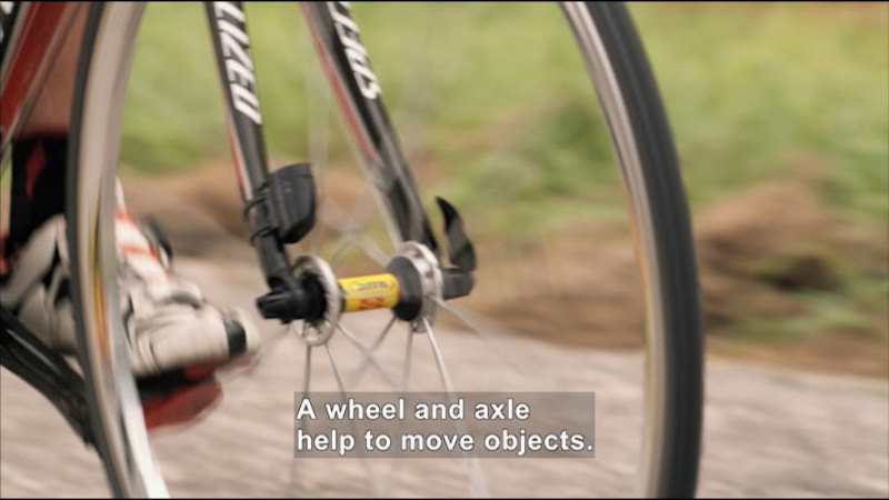 Close up of a bicycle tire. Caption:  A wheel and axle help to move objects.