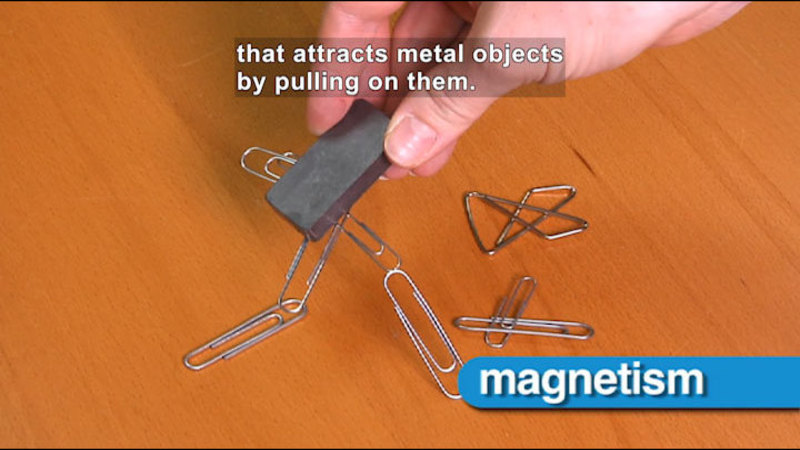 A magnet picking up paperclips. Caption: that attracts metal objects by pulling on them.