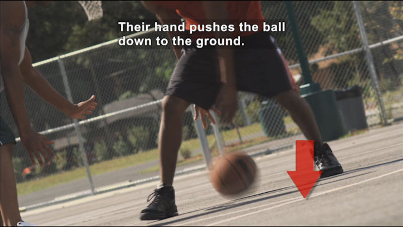 A man dribbling a basketball. Caption: Their hand pushes the ball down to the ground.