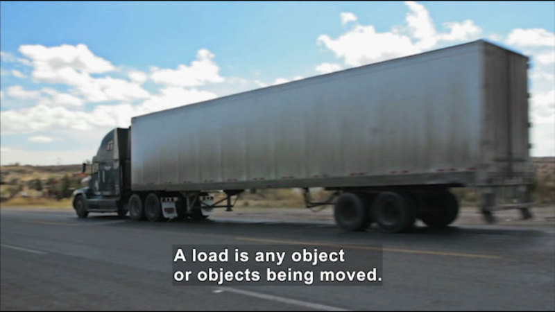 A semi-truck driving on a road. Caption:  A load is any object or objects being moved.