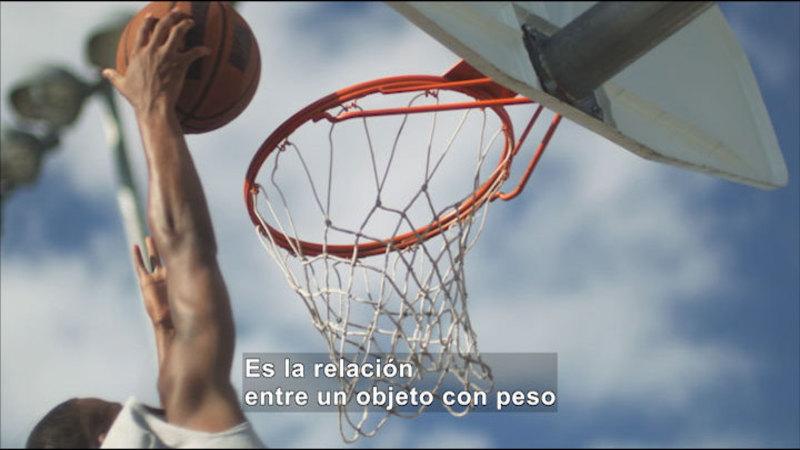 Man dunking a basketball. Spanish captions.