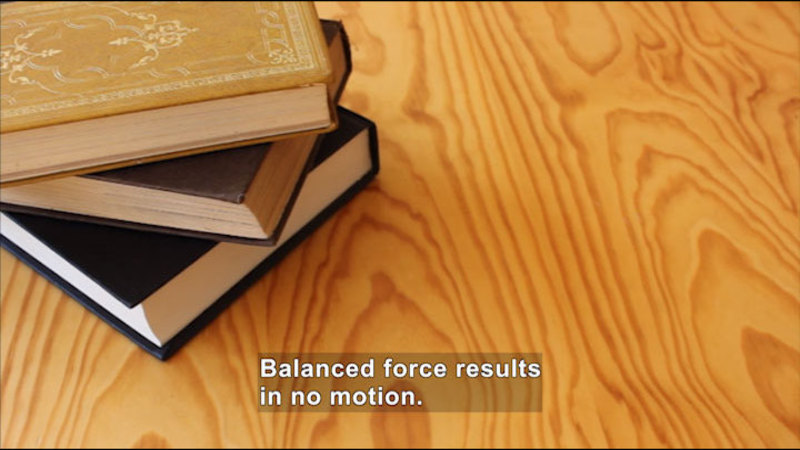 Three books stacked on a table. Caption: Balanced force results in no motion.
