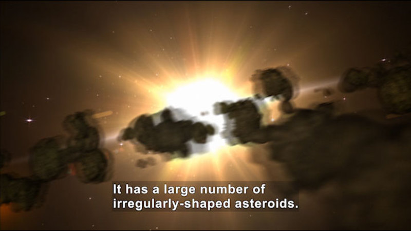 Asteroids moving through space. Caption: It has a large number of irregularly-shaped asteroids.