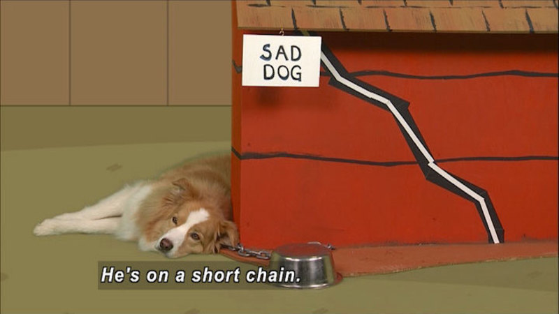 Dog laying at the front of a doghouse with a sign attached with Caption: sad dog. Food bowl is upside down by his head, chain attached to the ground and the dog. Caption: He's on a short chain.