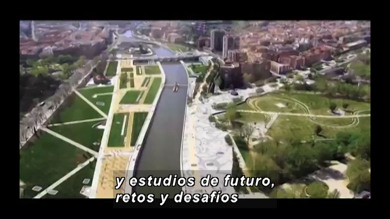 A channel of water blanketed by green spaces cuts its way through a big city. Spanish captions.