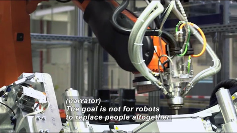 Robotic arm working on an object. Caption: (narrator) The goal is not for robots to replace people altogether.