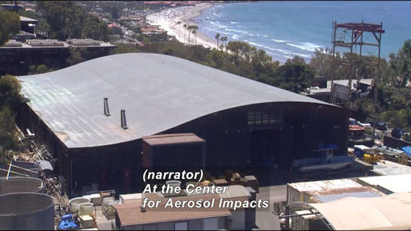 A large warehouse with a sloping roof. Caption: (narrator) At the Center for Aerosol Impacts