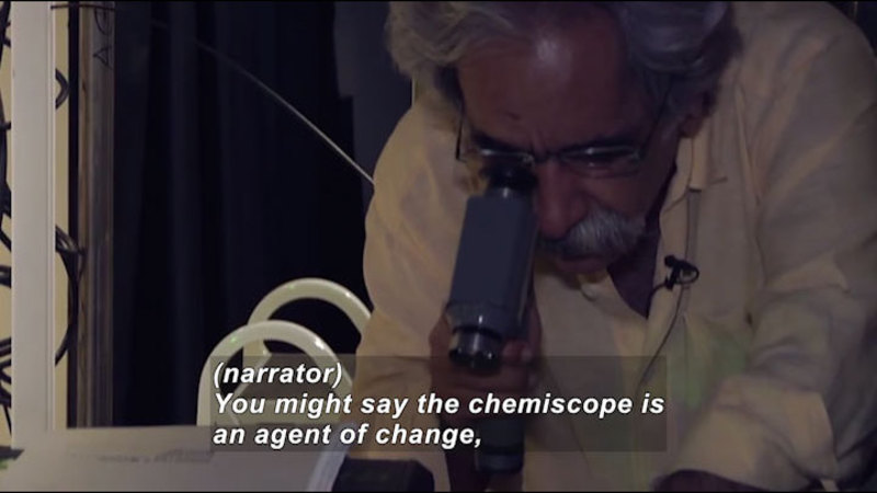 Person holding a tubular instrument to their eye. Caption: (narrator) You might say the chemiscope of an agent of change,