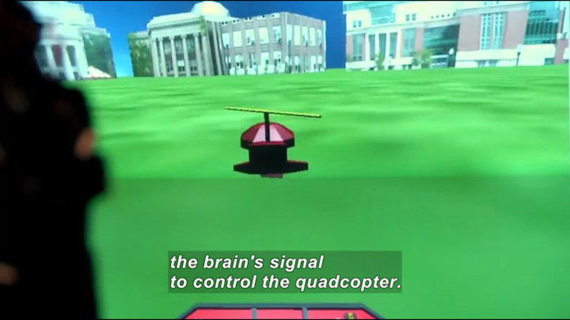 3D graphic of a mostly cylindrical object with a rotor on top against a backdrop of grass and buildings. Caption: the brain's signal to control the quadcopter.
