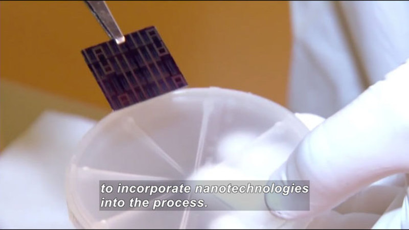 Gloved hand holding a round plastic object and putting an electronic chip into it. Caption: to incorporate nanotechnologies into the process.