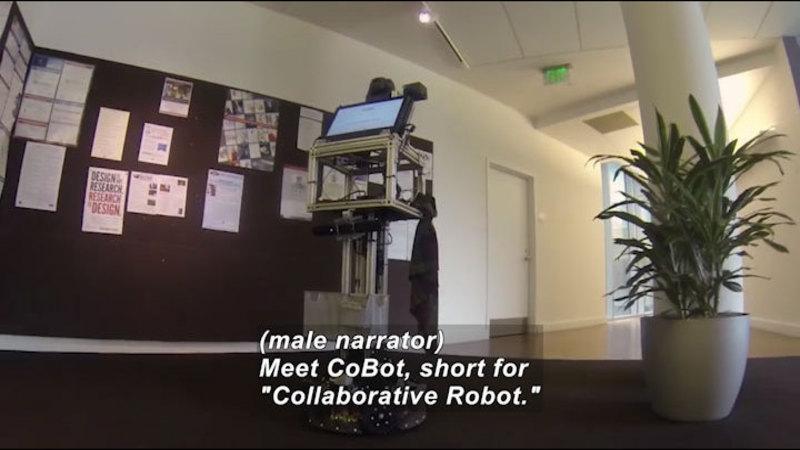 "Rectangular robot with a screen at eye level. Caption: (male narrator) Meet CoBot, short for ""Collaborative Robot."""