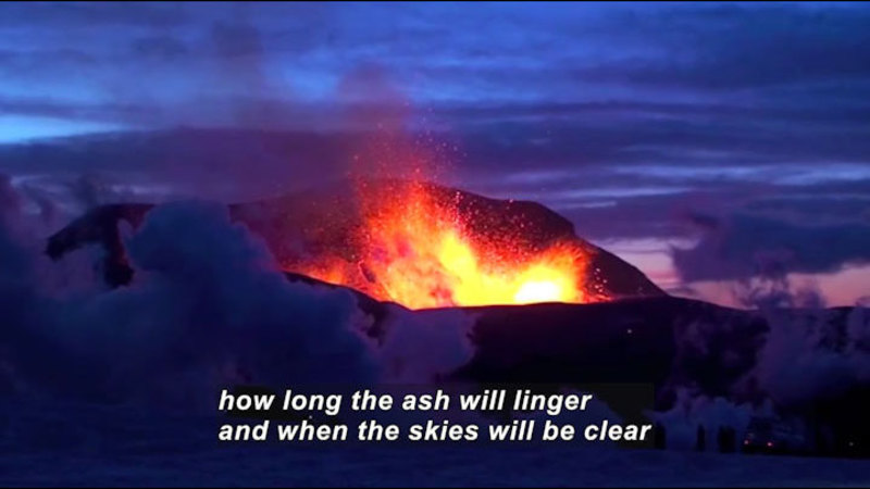 Lava spewing from a crevasse while smoke and ash rises around it. Caption: how long the ash will linger and when the skies will be clear