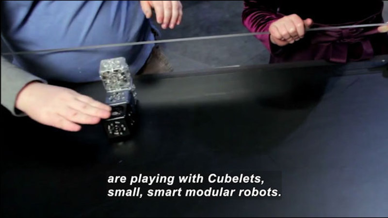 Person touching an object made of stacked and connected cubes. Caption: are playing with Cubelets, small, smart modular robots.