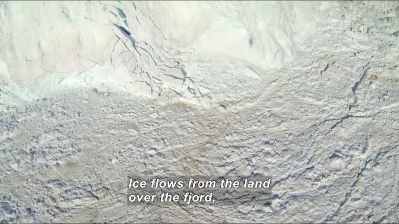 Aerial view of ice breaking apart as it flows onto land from an ice shelf. Caption: Ice flows from the land over the fjord,
