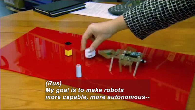 Person adjusting objects on a table next to a mechanical object with legs. Caption: (Rus) My goal is to make robots more capable, more autonomous--