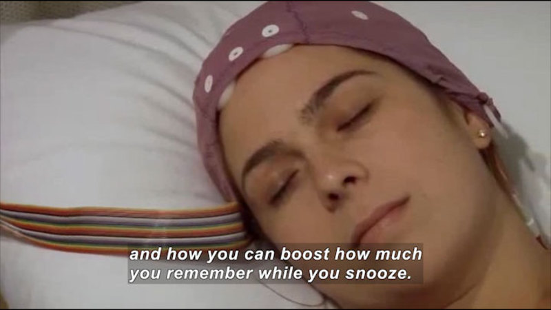 Person with head laying on pillow while wearing a cap with wires attached. Caption: and how you can boost how much you remember while you snooze.