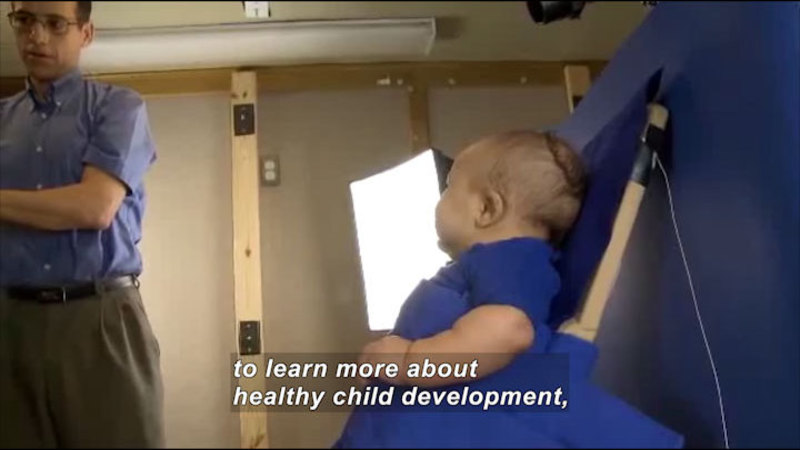 Toddler leaning against a blue background under bright lights while an adult stands by. Caption: to learn more about healthy child development,