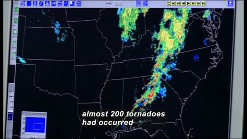 Computer screen showing east coast of United States with color gradient showing a band of storms parallel to the coastline. Caption: almost 200 tornadoes had occurred