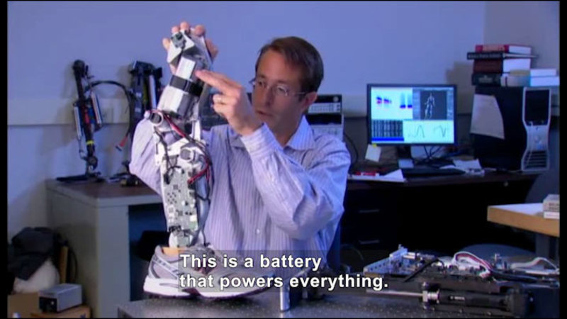 Person working on a robotic leg that is wearing a shoe. Caption: This is a battery that powers everything.