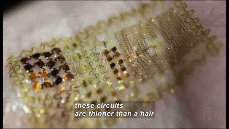 Closeup view of very thin wires forming concentric squares and other geometric patterns. Caption: these circuits are thinner than a hair