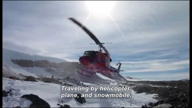 Helicopter hovering over a rocky, snow covered landscape. Caption: Traveling by helicopter, plane, and snowmobile,